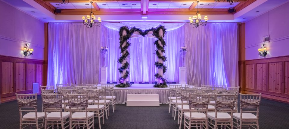 Grand Ballroom set up with a small stage and well-appointed decoration and lighting for a wedding