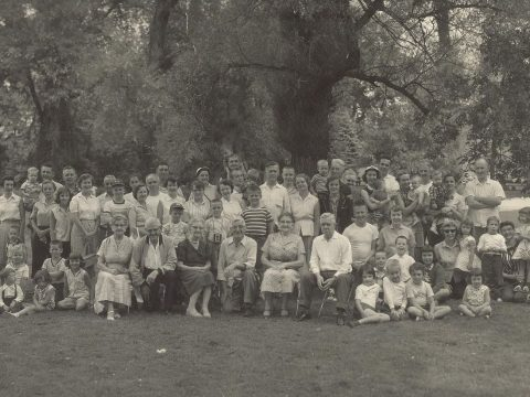A large family poses together at a reunion in a park sometime in the early 20th century