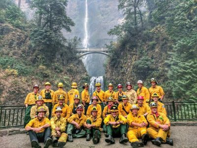 The Firefighters Who Saved Multnomah Falls Lodge stand in front of the waterfall